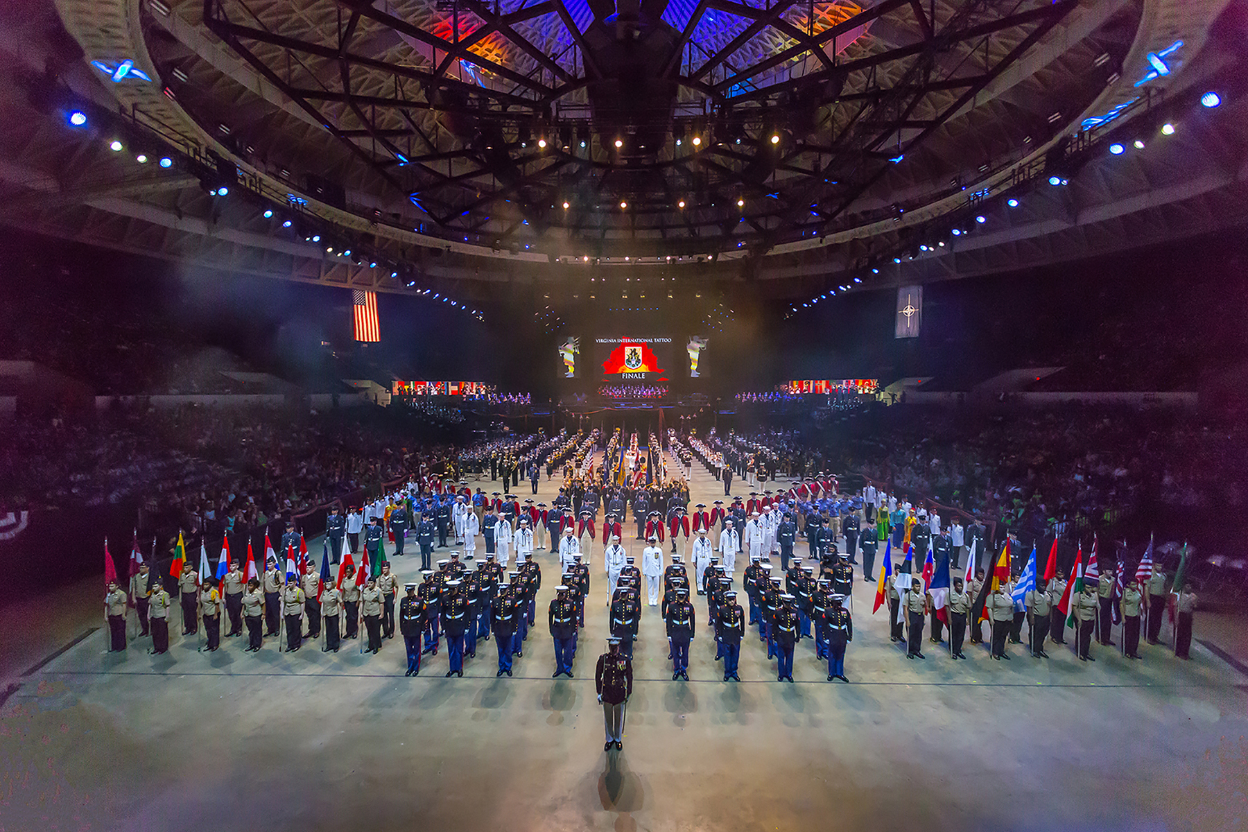 Uniformed military members and musicians of various services and branches from different nations, and costumed civilian performers, fill the floor of a large dome-ceilinged arena.