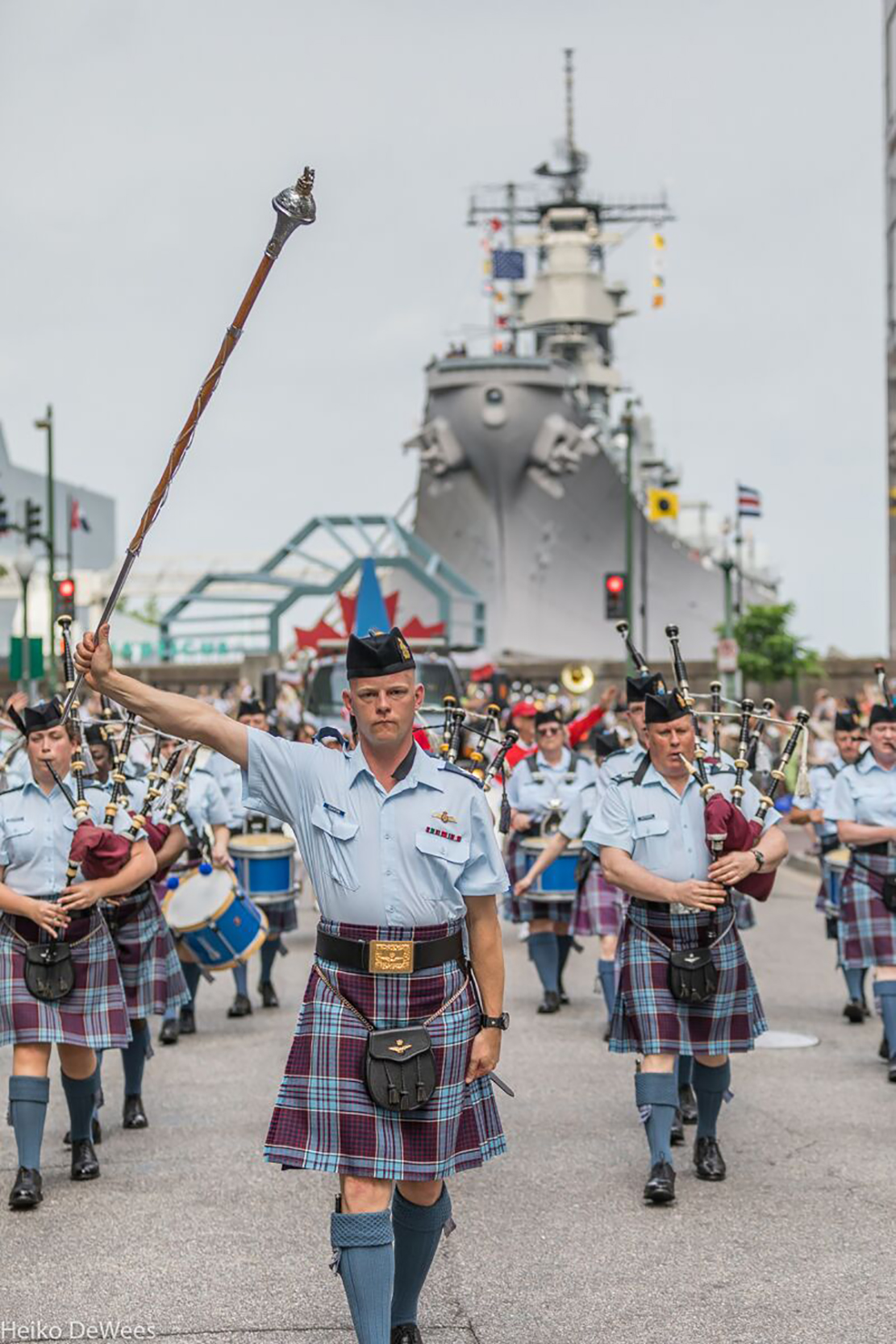 Drum Major Ian Cleaton of 8 Wing Trenton raises the mace as he leads the RCAF Pipes and Drums during the NATO-fest Parade in downtown Norfolk, Virginia, with the historic USS Wisconsin alongside in the background. PHOTO: Heiko DeWees