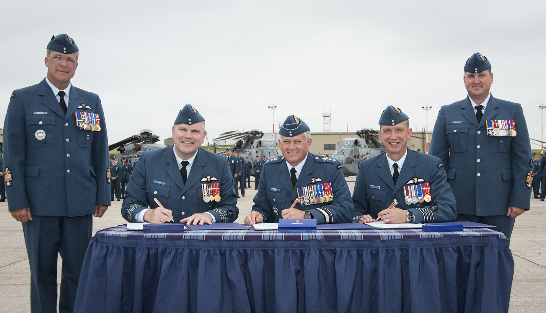 Sitting outdoors at a table covered with a tartan cloth, three men in blue uniforms hold pens and prepare to sign a document each. A man in a blue uniform stands at each ed of the table.