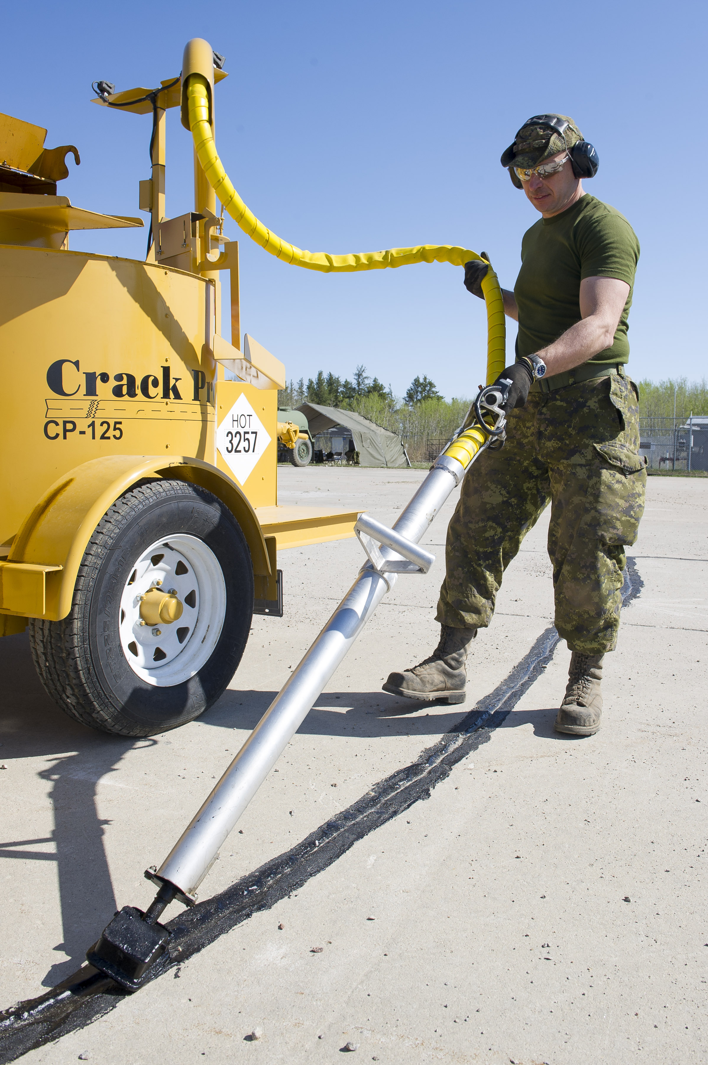 Corporal Steve Guay of 2 Wing Bagotville, Quebec, fills a crack in a concrete runway with hot oil during the Airfield Light Repair course held at 4 Wing Cold Lake, Alberta, from May 8 to 19, 2017. PHOTO: Corporal Justin Roy, CK07-2017-0348-003