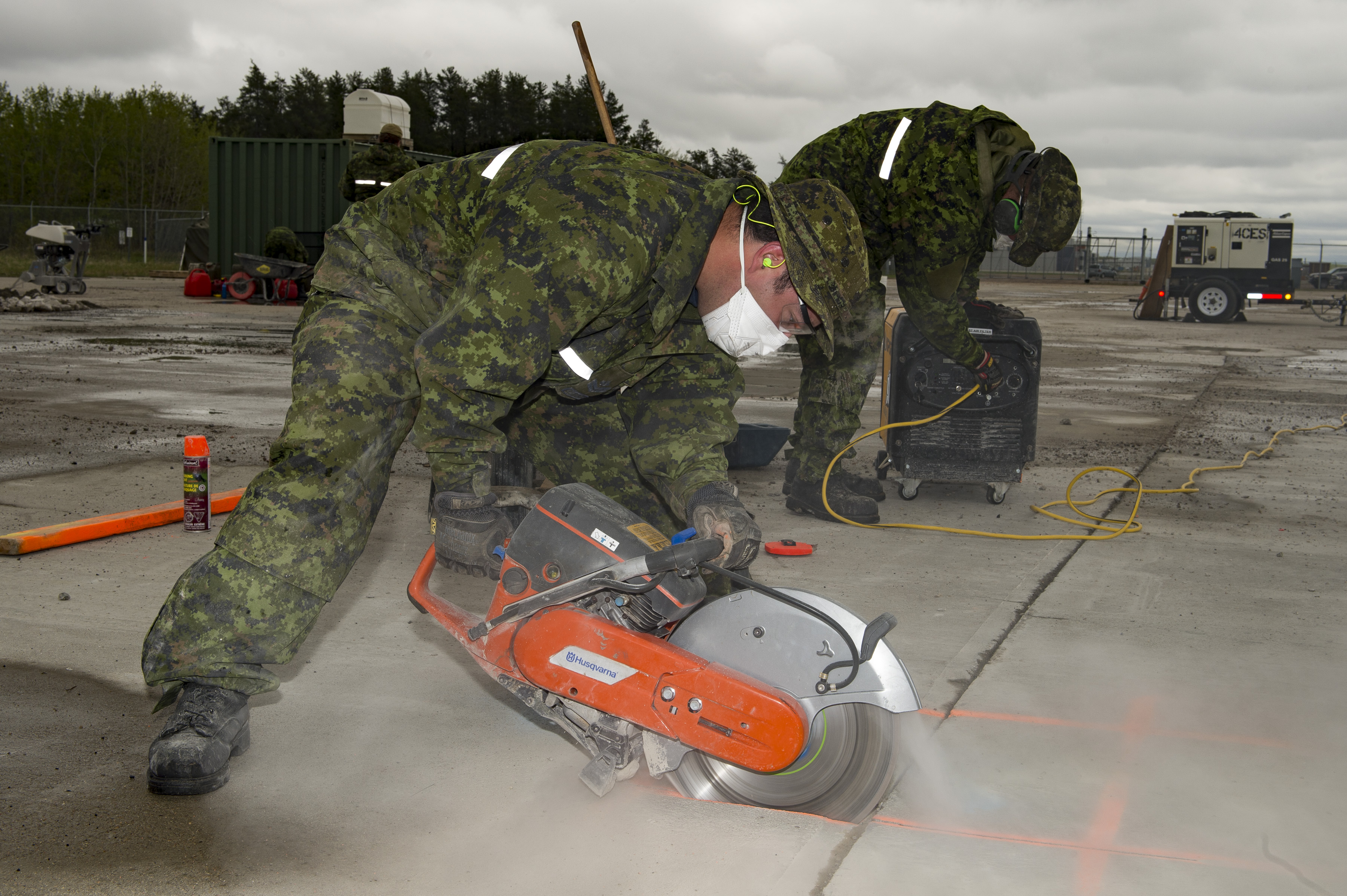 Master Corporal Keven Black of 2 Wing Bagotville, Quebec, using a concrete saw, cuts a portion of runway to be repaired during the Airfield Light Repair course held at 4 Wing Cold Lake, Alberta, from May 8 to 19, 2017. PHOTO: Corporal Justin Roy, CK07-2017-0348-007