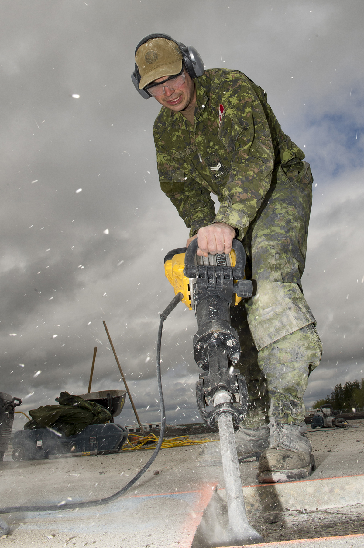 A man in a green camouflage uniform uses a jackhammer to remove concrete.