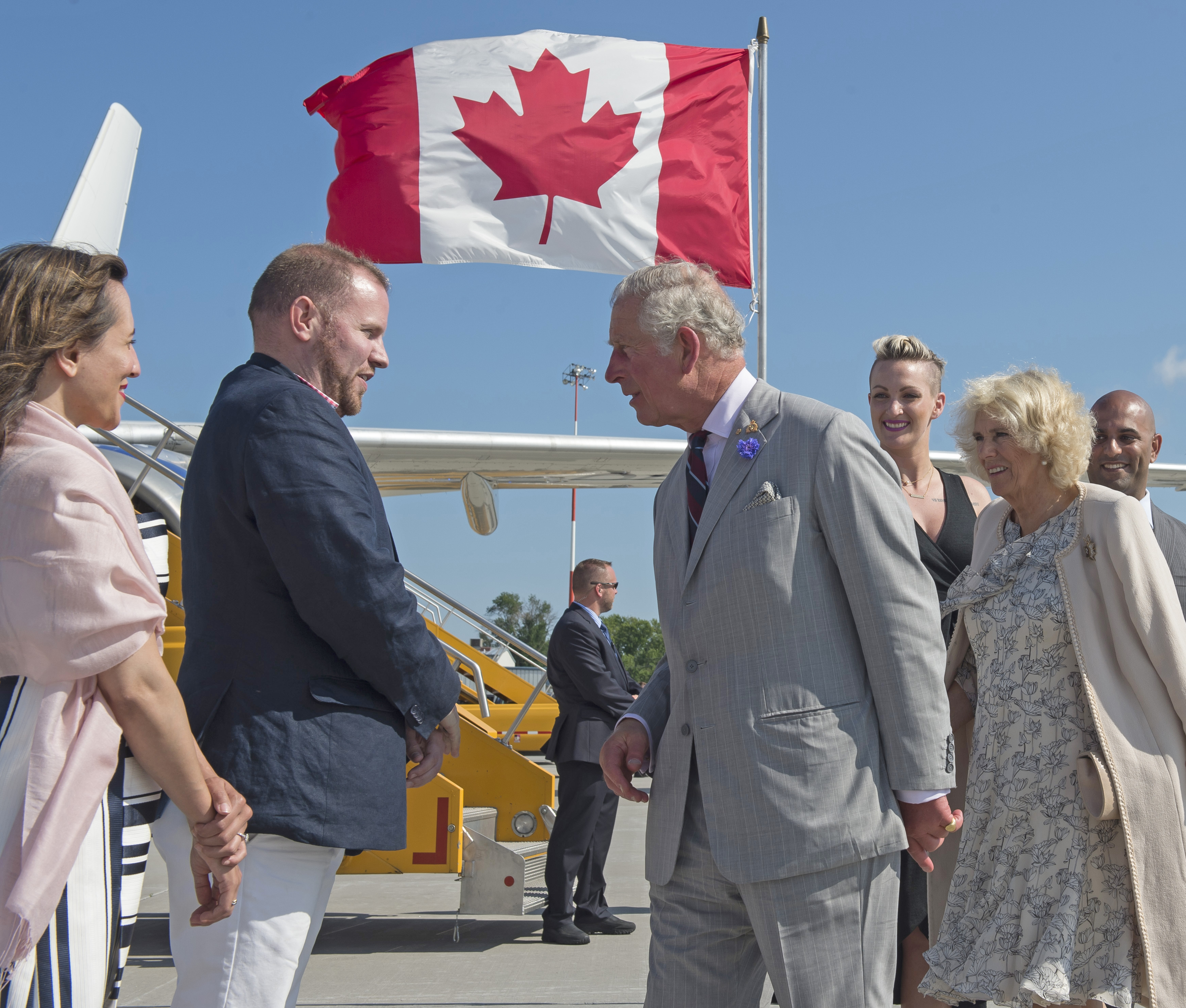 Prince Charles, accompanied by Camilla, Duchess of Cornwall, pauses to speak with Tom Spence and Leen Al-Zaibak from the Ontario Government as they prepare to board an RCAF Polaris aircraft to travel from 8 Wing Trenton to Ottawa, Ontario, on June 30, 2017. PHOTO: Corporal Ryan Moulton, TN11-2017-0398-033
