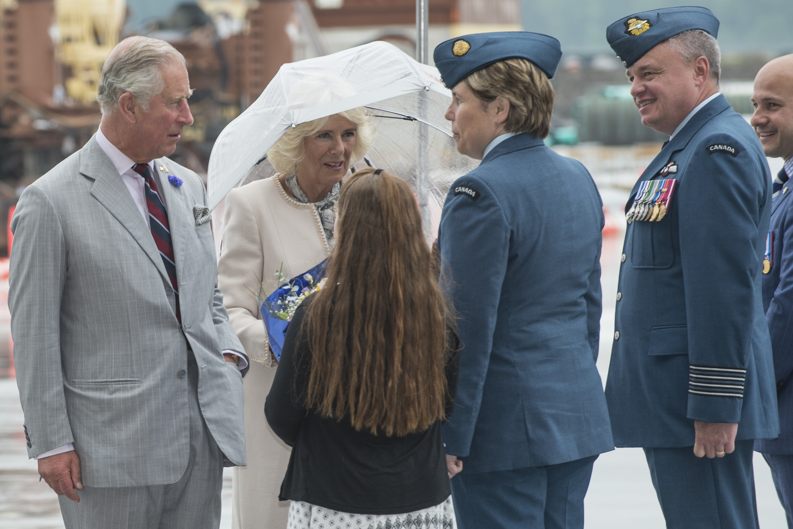 A man in a gray suit and a woman in a light coloured suit, holding an umbrella, speak with a woman in a blue uniform and a young girl with long hair.