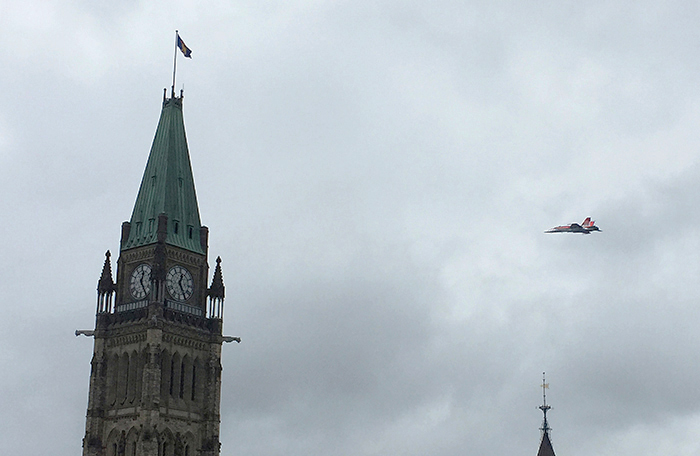 A jet aircraft flies toward and behind an old stone clock tower.