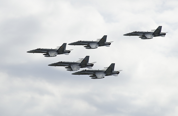 slide - Five ffighter aircraft fly in formation in an overcast sky.