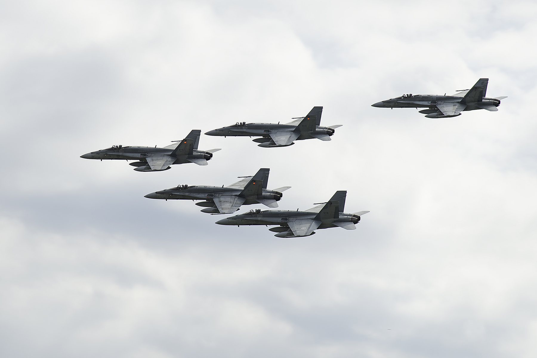 Five ffighter aircraft fly in formation in an overcast sky.