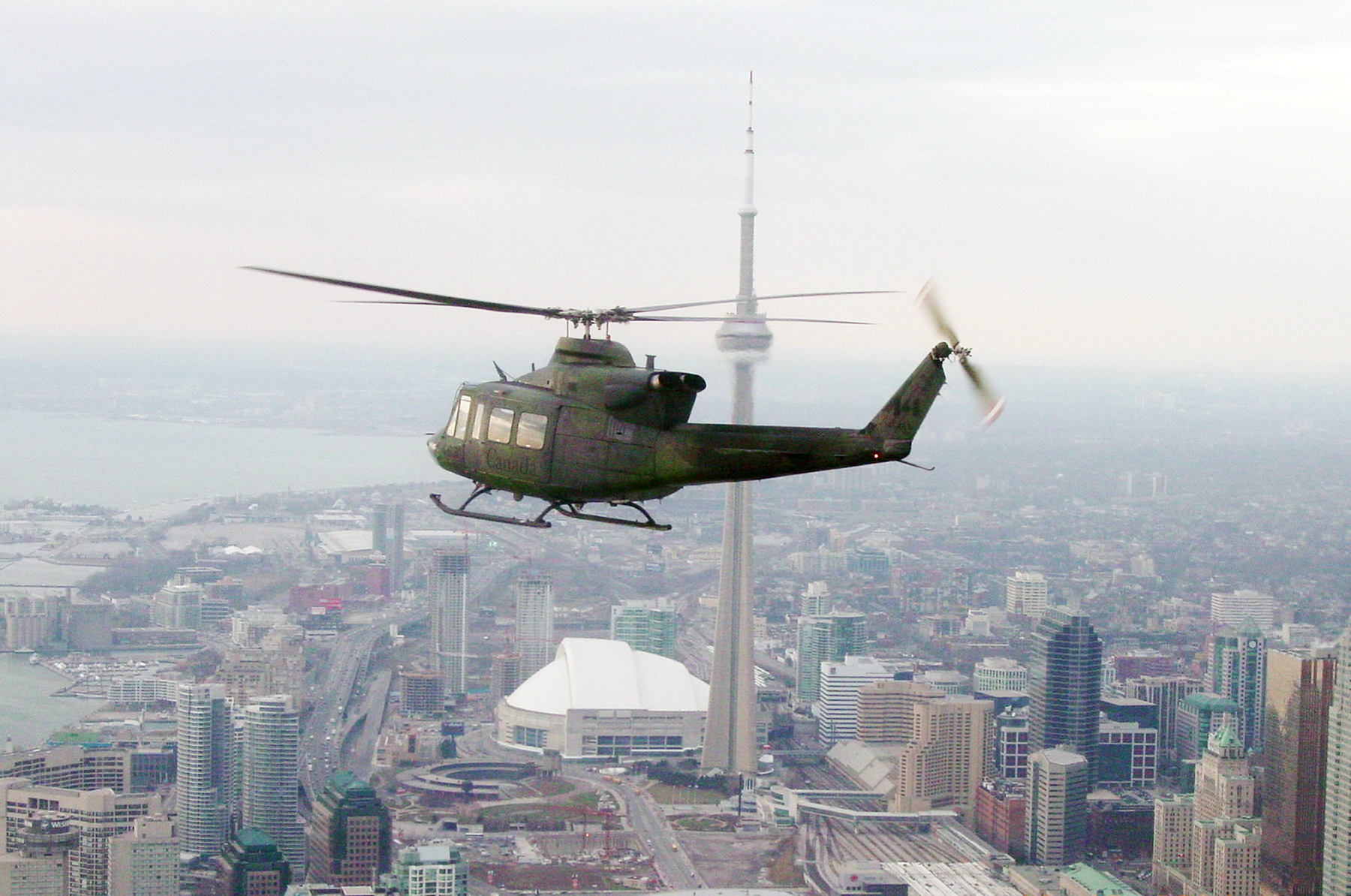 A CH-146 Griffon helicopter from 1 Wing Kingston, Ontario's 400 Tactical Helicopter Squadron, piloted by Captain Harry Ollmann, with co-pilot Captain Paul Reid and flight engineer Corporal Ian Johnston, flies over downtown Toronto on December 16, 2005, bound for Sick Children's Hospital to deliver Christmas gifts and fun. Every year, 1 Wing elves organize and deliver gifts collected from military members and the local community to brighten the day for young patients unable to spend Christmas at home with their families. PHOTO: Master Corporal Larry Wilson, DND Archives, FA2005-0183a