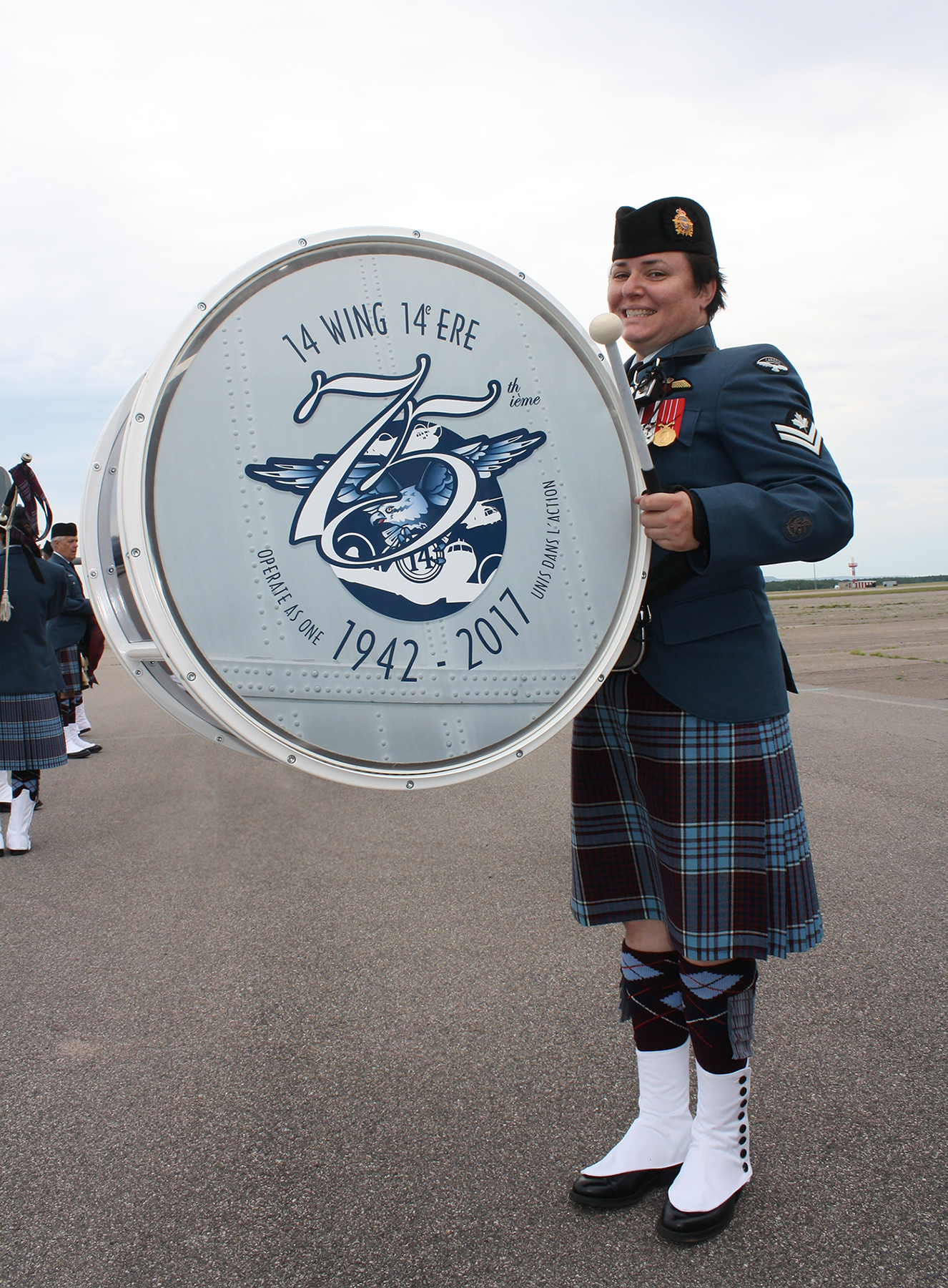 A drummer in Scottish regalia stands with her bass drum, while other band members in regalia stand in the background.