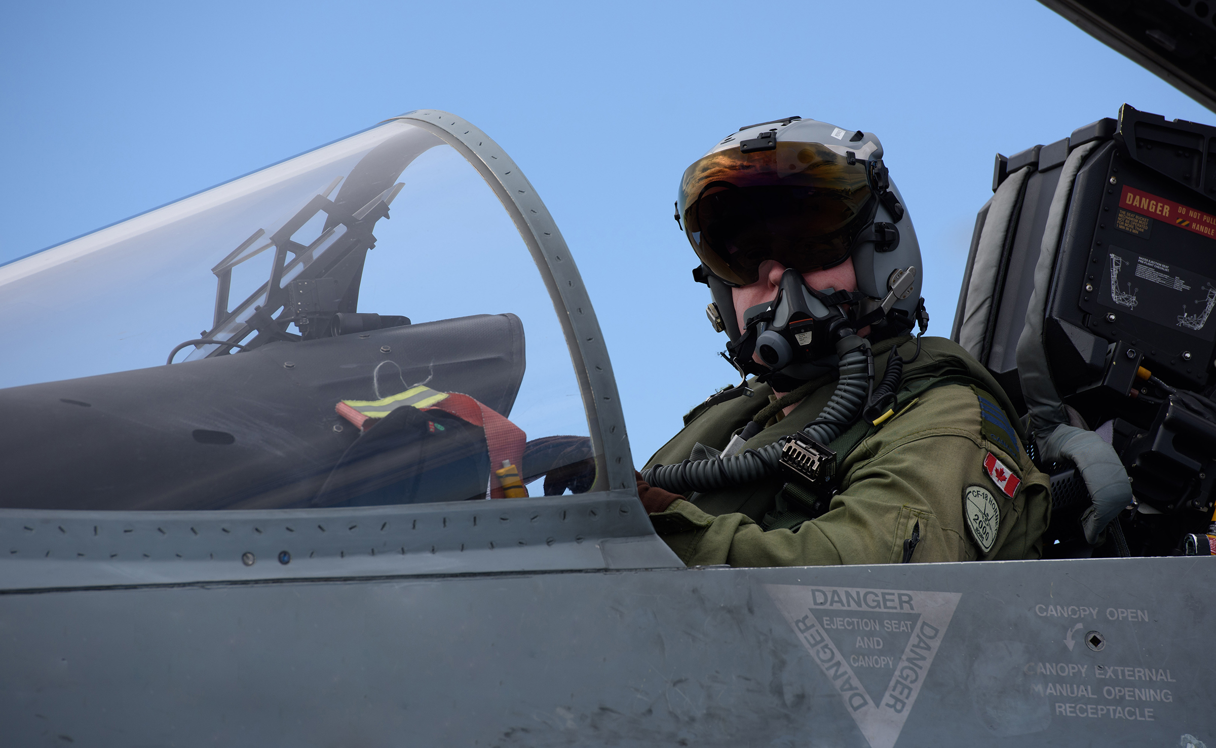 A person wearing a helmet with a visor and oxygen mask covering his face sits in the cockpit of a fighter aircraft with the canopy open.