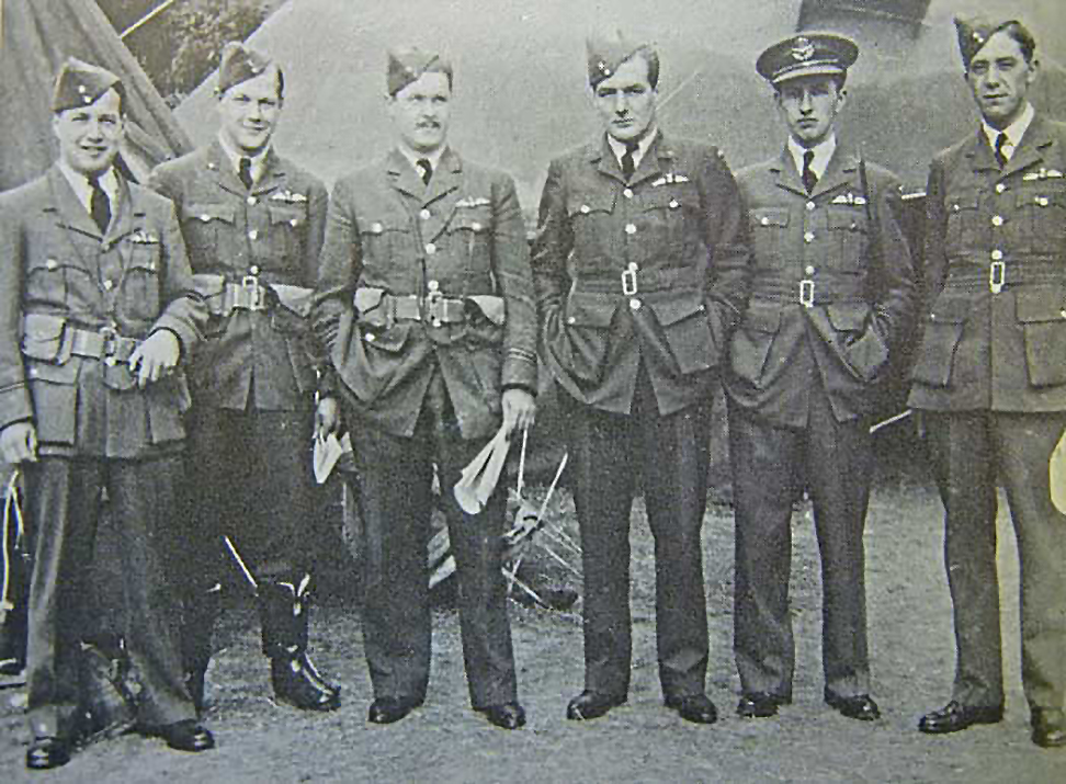In a black and white photograph, six uniformed men stand in a line and face the camera.