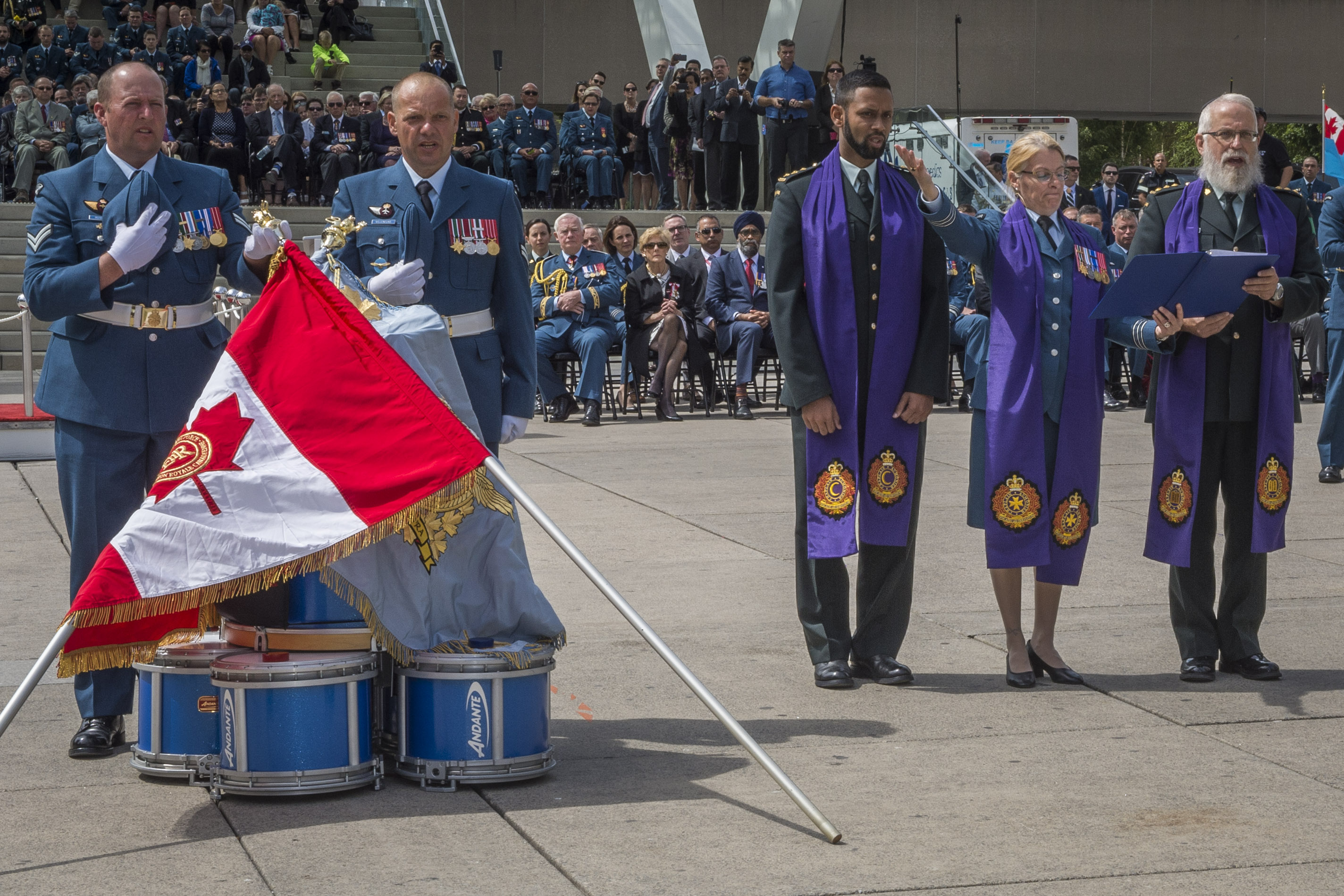 The RCAF chaplain, Lieutenant-Colonel Martine Bélanger, accompanied by Imam Captain Ryan Carter (left) and Rabbi Captain Lazer Danzinger (right), consecrates the RCAF's new Colours on September 1, 2017. Through this means, the Colours are sanctified and devoted to service as symbols of honour and duty. Further, all members of the Royal Canadian Air Force, through those on parade, rededicate themselves to the ideals the Colours represent. PHOTO: Corporal Alana Morin, FA03-2017-0114-001