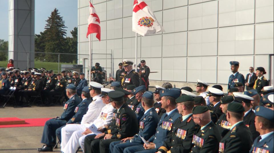 A man in a military uniform stands behind a podium, amid a large group of seated people wearing a variety of military uniforms