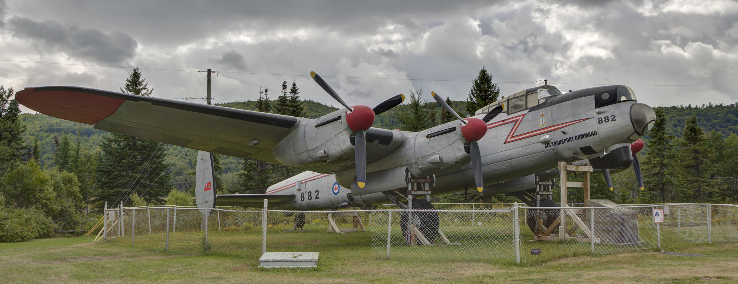 A large grey aircraft with four propellers on its wings rests on grass behind a fence.