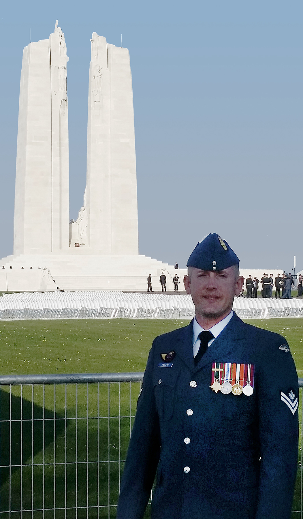A man in a blue uniform stands in front of a chain link fence; in the distant background is an enormously tall monument comprising two pylons with sculpted figures. People are assembled at the base of one of the pylons.
