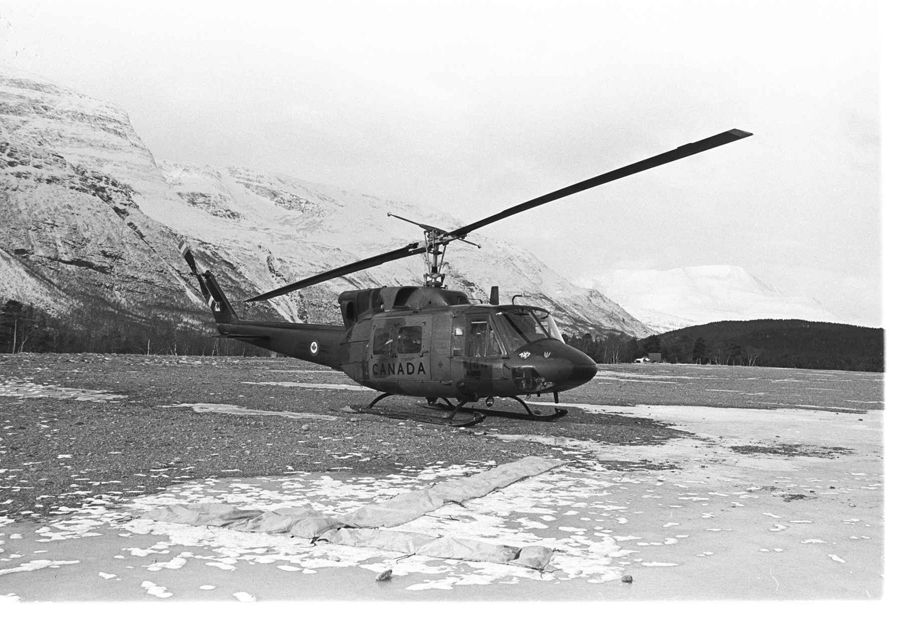 Deployed on Exercise Alloy Express, an RCAF CH-135 Twin Huey helicopter from 427 Squadron sits on an alpine lakeshore in the Norwegian mountains on March 15, 1982. PHOTO:  Sergeant J.C. Rodger, IS82-573