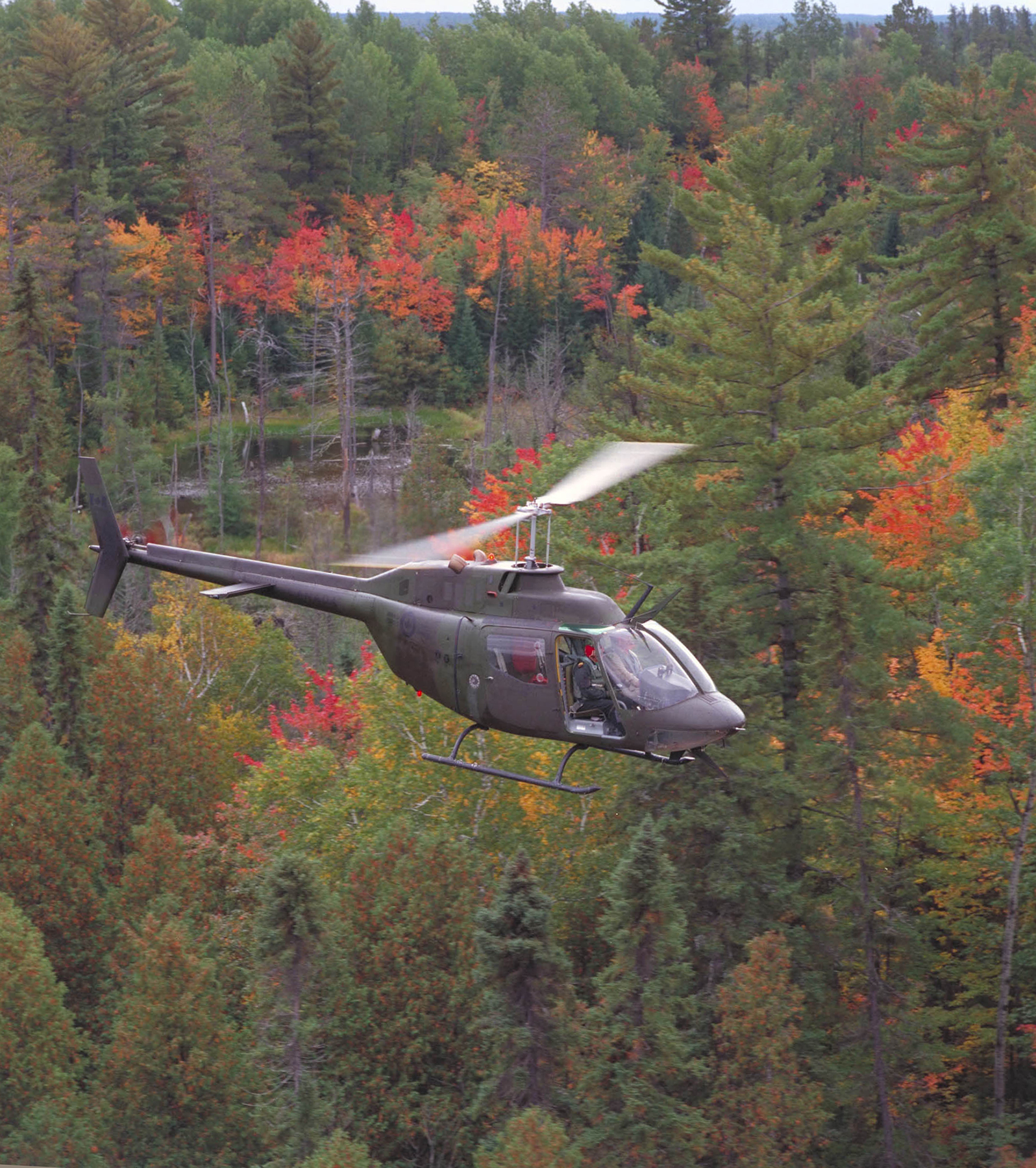 A CH-136 Kiowa from 427 Tactical Helicopter Squadron flies over autumn trees at Canadian Forces Base Petawawa, Ontario, on September 21, 1988. PHOTO: Warrant Officer Vic Johnson, ISC88-971