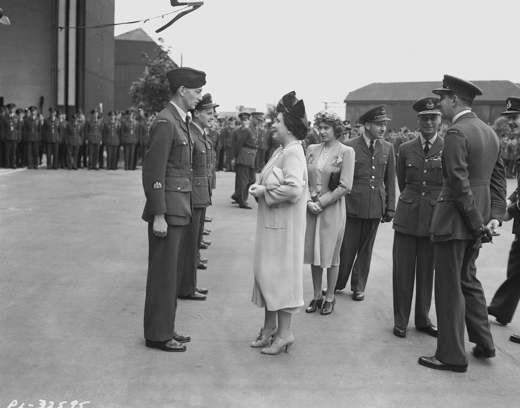 "In an undated photograph, Queen Elizabeth talks with Warrant Officer 1st Class J.S. Niven, the navigator of a 427 ""Lion"" Squadron Halifax bomber that was hit by a 500-pound (226.8-kilogram) bomb from another aircraft during a night raid over Germany. King George VI (centre right) smiles at the photographer while Princess Elizabeth stands in the background. PHOTO: DND Archives, PL-32595"