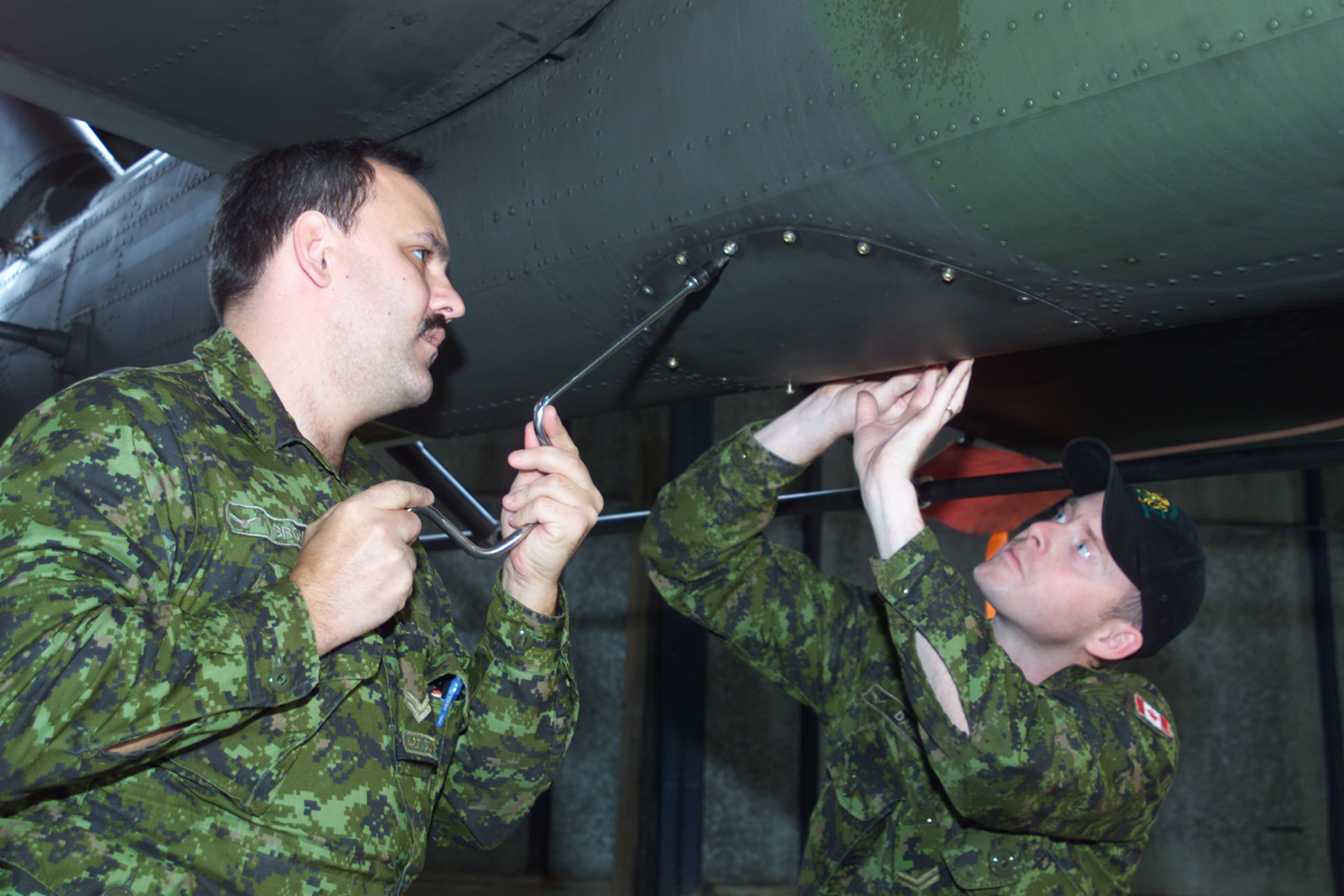 427 Squadron aircraft technicians Corporal Gerald Browne, from Guelph, Ontario, and Corporal Ian Daniels, from Mount Pearl, Newfoundland and Labrador, replace a panel on the underside of a CH-146 Griffin helicopter on November 16, 2002, in Velika Kladusa, Bosnia and Herzegovina, where 1,450 Canadians were deployed with NATO's Stabilization Force to enforce the peace in the region. PHOTO: Corporal John Clevett, VK2002-0229-01d