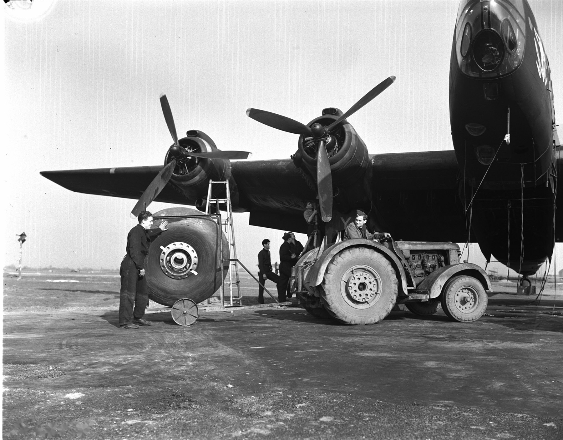 "427 ""Lion"" Squadron groundcrew change out a wheel on a Handley Page Halifax B MK III at an airfield in England during the Second World War. PHOTO: DND Archives, PL-28518"