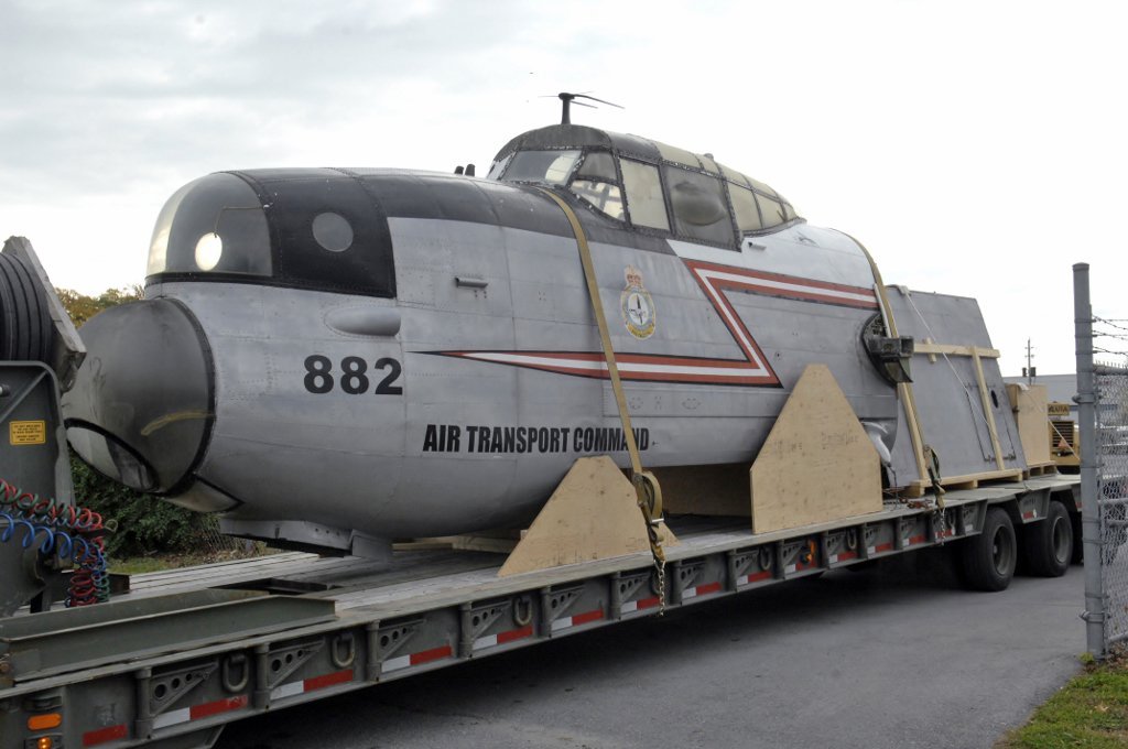 The nose and cockpit of a large grey aircraft, severed from the rest of the aircraft, rests on the back of a flatbed truck trailer.