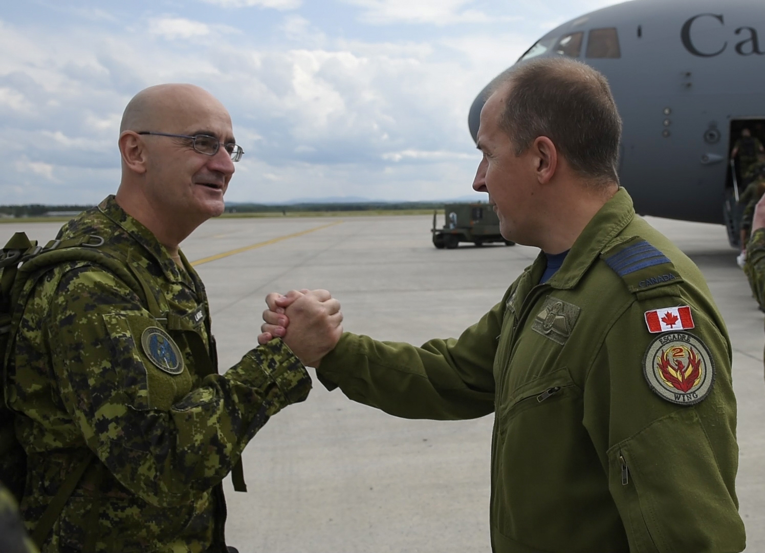Colonel Luc Guillette (right), commander of 2 Wing Bagotville, Quebec, bids farewell to Chief Warrant Officer, Jean Lavoie, chief warrant officer of the Airfield Activation Surge Team (AFAST), as he departs from Bagotville enroute to Romania on August 11, 2017. PHOTO: Master Corporal Louis Brunet, BN25-2017-0484-015