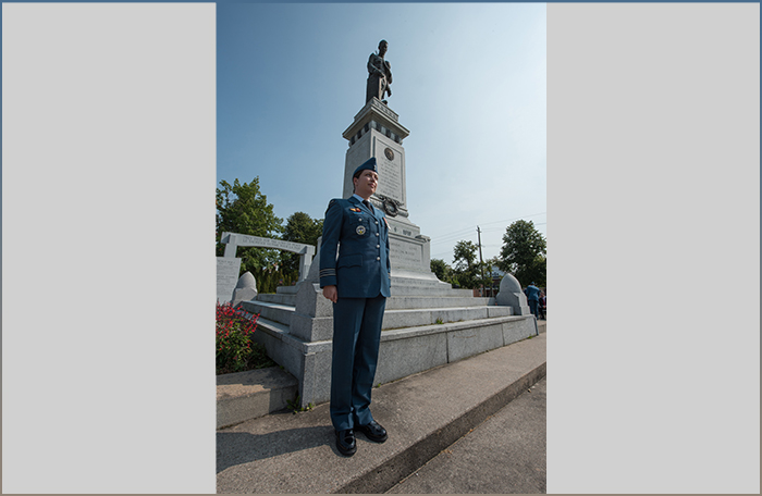 slide - A woman wearing a medium-blue uniform stands at attention at the right front corner of a tall memorial topped with a statue and backed by trees.