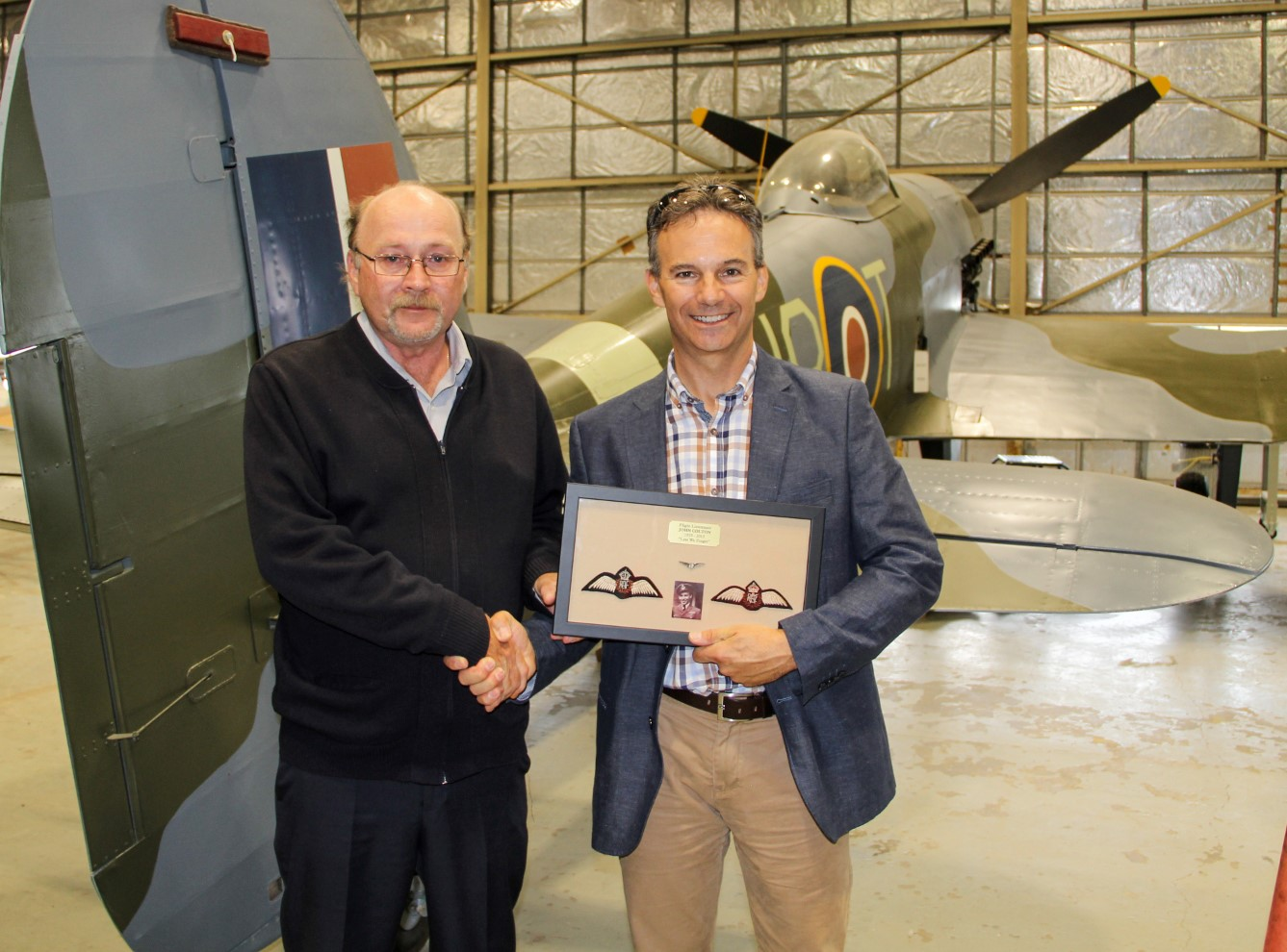 At the Canada Aviation and Space Museum, Mr. John Colton, Jr. (left), makes a presentation to Major (retired) Francis Mercier for his contribution to the creation of a work of art honouring Flight Lieutenant John Colton. PHOTO: Courtesy Jean Lacroix