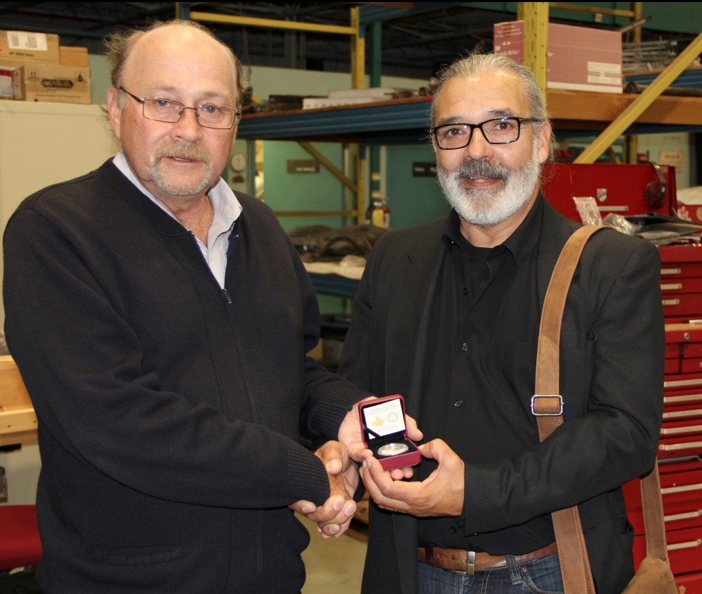 At the Canada Aviation and Space Museum in Ottawa, Mr. John Colton, Jr. (left), presents artist Mr. Jean Lacroix with a commemorative coin from the Royal Canadian Mint as a token of appreciation for the portrait montage Mr. Lacroix created honouring the war-time service of Flight Lieutenant John Colton. PHOTO: Courtesy Mr. Jean Lacroix