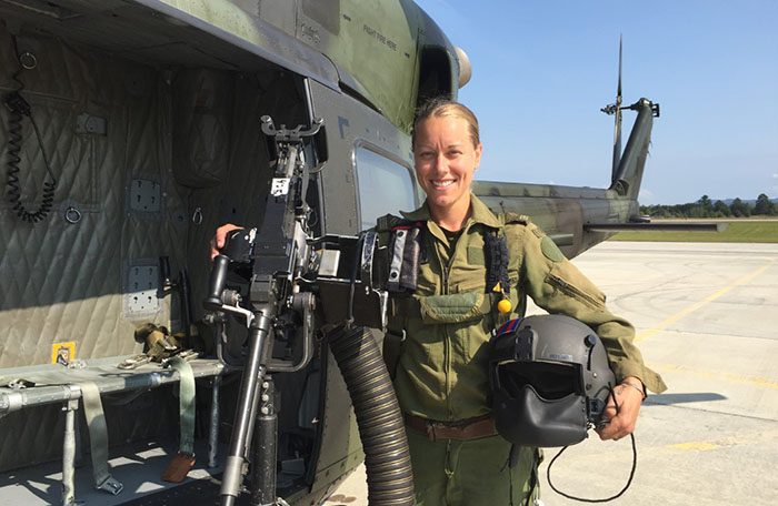 slide - A woman wearing olive green flying clothing stands next to a green and black military helicopter. She holds a flight helmet under her right arm and her left hand rests on a large machine gun mounted on a stand.