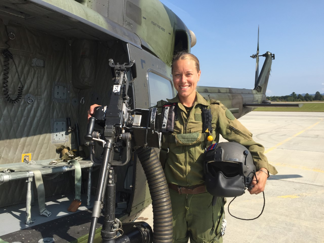 A woman wearing olive green flying clothing stands next to a green and black military helicopter. She holds a flight helmet under her right arm and her left hand rests on a large machine gun mounted on a stand.