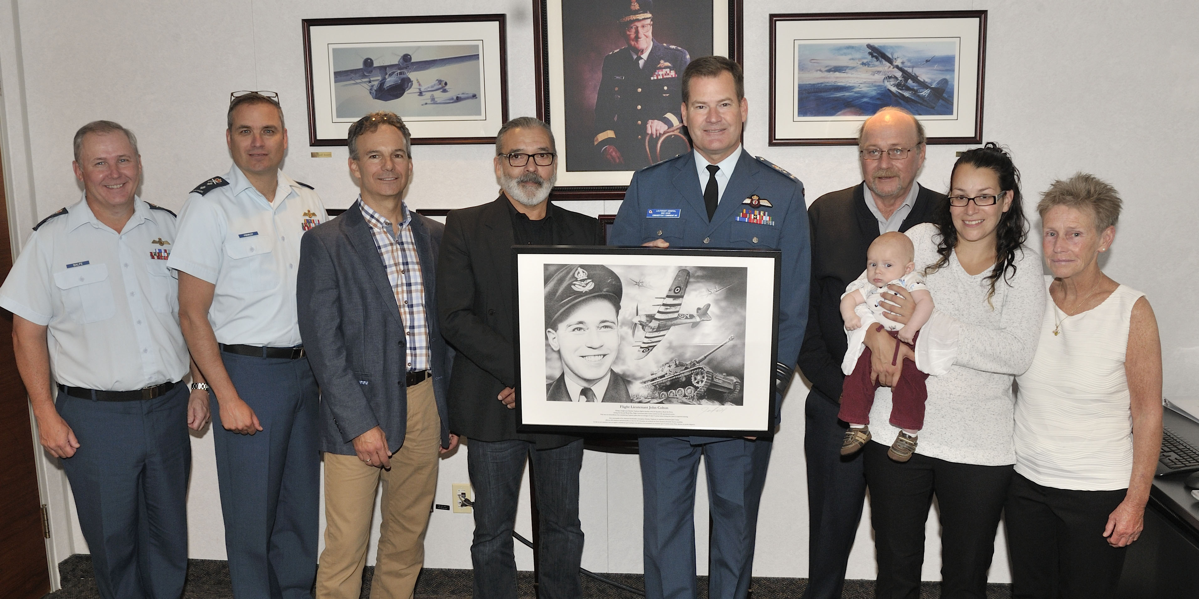 The commander of the Royal Canadian Air Force accepted the print of a portrait of Flight Lieutenant John Colton from the artist and the Colton family on October 5, 2017. From left to right: Brigadier-General Todd Balfe, Special advisor fighter capability; Major-General Blaise Frawley, deputy commander of the RCAF; Major (retired) Francis Mercier, artist Jean Lacroix, RCAF commander Lieutenant-General Mike Hood, and members of the Colton family: John, Jr., Brian (aged three months), Stephanie and Nancy. PHOTO: Corporal Vic Lefrançois, FA01-2017-0011-01