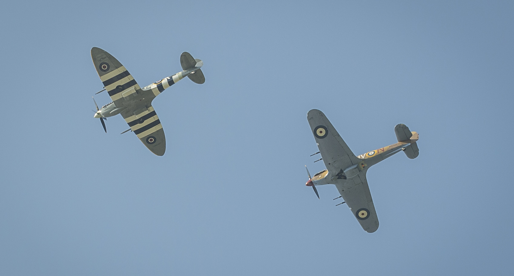 "Following the two minutes of silence and the playing of ""Rouse"", a Spitfire Mk IX (left)  and a Hurricane Mk IV from Vintage Wings of Canada fly over the parade as a piper plays ""The Flowers of the Forest"" (""Piper's Lament""). PHOTO: Corporal Alana Morin, FA03-2017-0119-058"