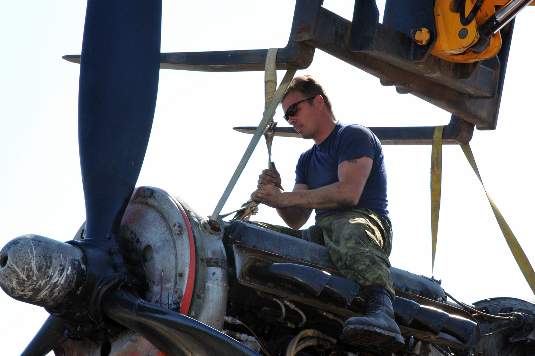 An RCAF technician from ATESS tightens straps on one of KB882's engines in preparation for its removal. PHOTO: Warrant Officer Fran Gaudet