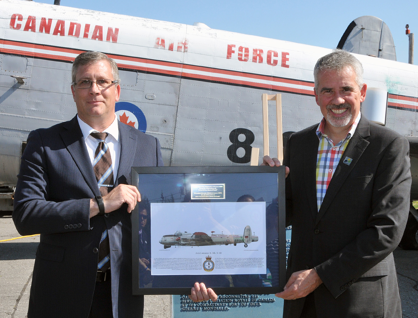 The curator of the National Air Force Museum of Canada, Kevin Windsor (left), presents Edmundston mayor Cyrille Simard with an artist's concept of how KB882 will appear following its restoration. PHOTO: Warrant Officer Fran Gaudet