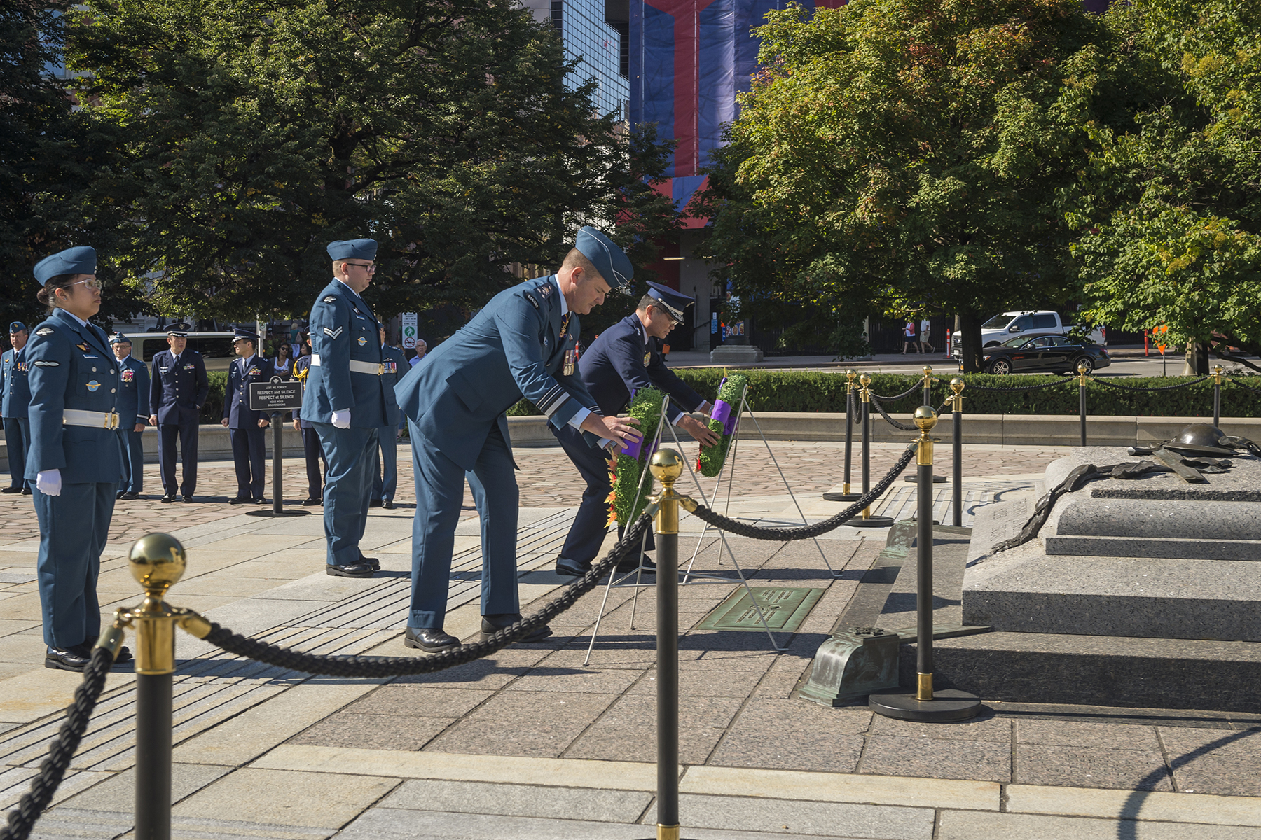 In a public square in a downtown area, two men in blue uniforms, one darker blue than the other, lay wreaths in front of ranks of other men in blue uniforms..