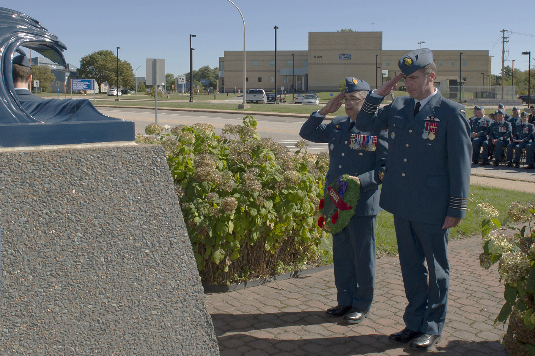 Two men, one holding a wreath, wear medium-blue uniforms with poppies and salute at a stone memorial, while many more people in similar uniforms stand in the background