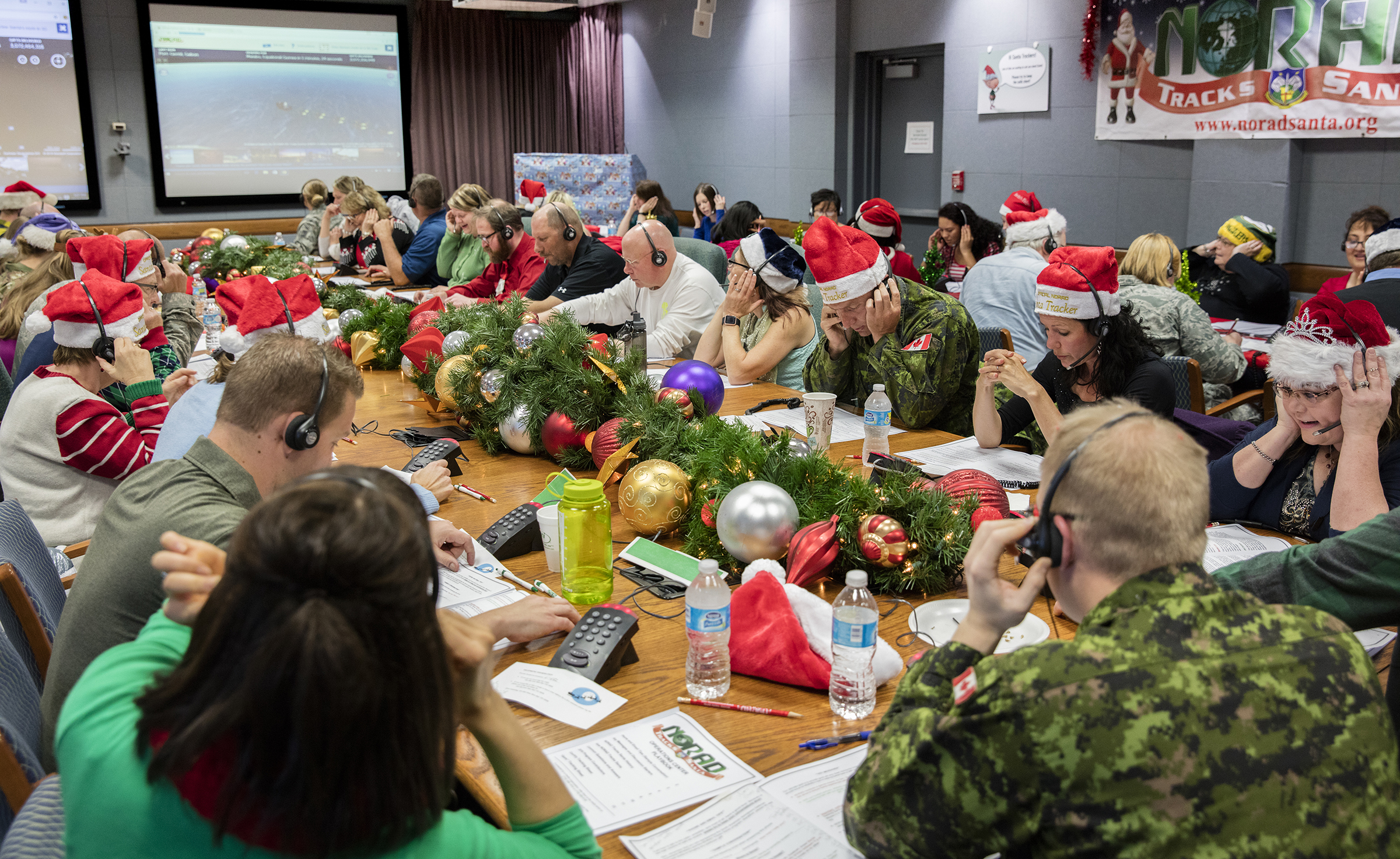 In a large room, people wearing military uniforms and civilian clothing, sit around large tables covered in holiday decorations and talk on telephones. Many are wearing Santa Claus-type hats.