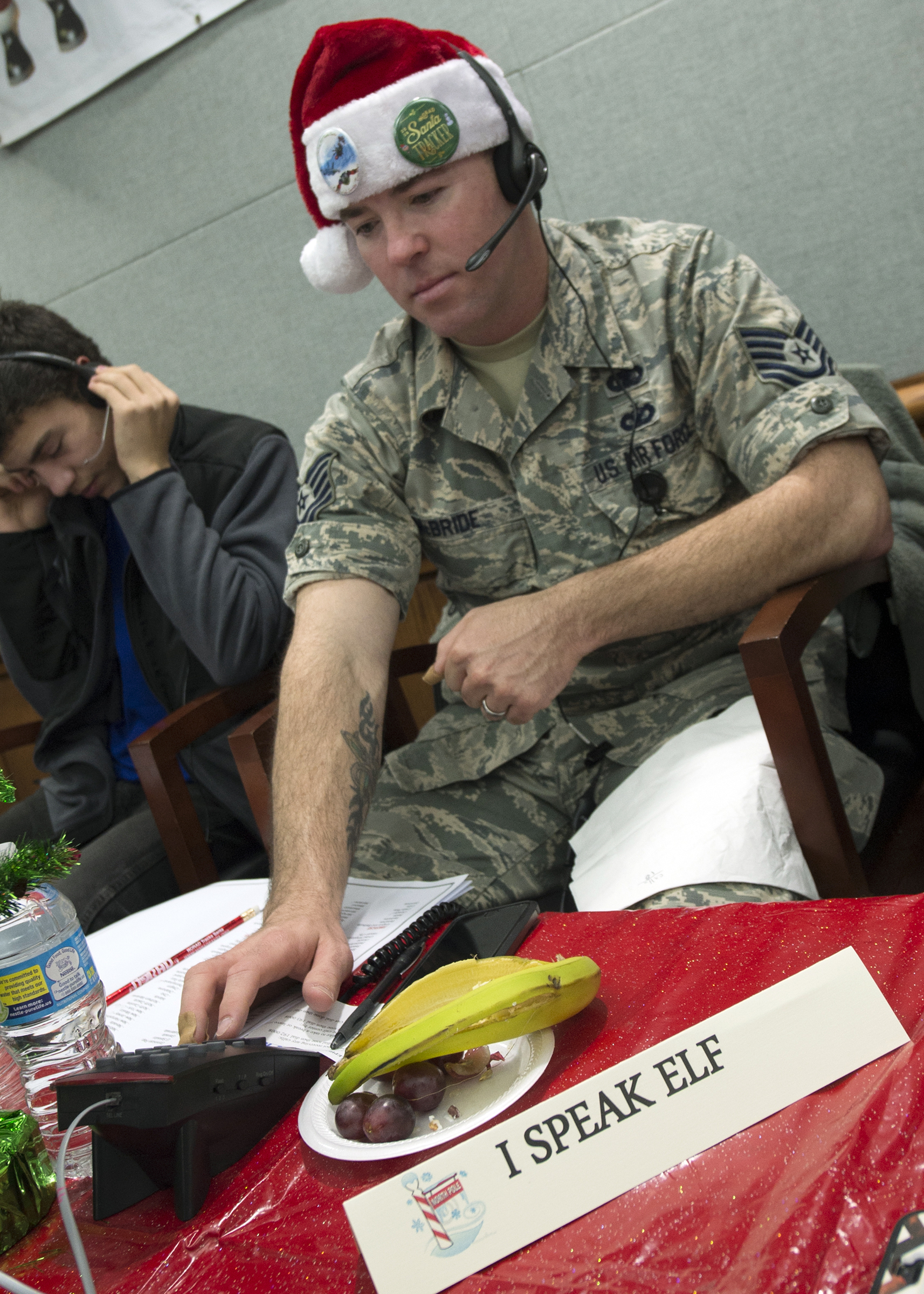 "An American serviceman is ready just in case he gets a call directly from the North Pole during the 2016 NORAD Tracks Santa Event at Peterson Air Force Base in Colorado on December 24 as the sign in front of him reads ""I SPEAK ELF"". PHOTO: Dennis Carlyle, NORAD, 161224-F-ZZ999-010"