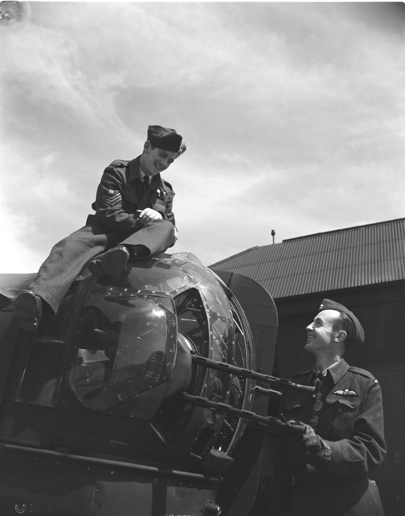 Flight Sergeant P.F. Hunt, atop the rear turret of his Bison Squadron Halifax, is congratulated by his skipper, Flying Officer Duncan McNaughton, for shooting down a Junkers Ju-88 during a mission against rail yards near Paris. PHOTO: DND Archives, PL-31647