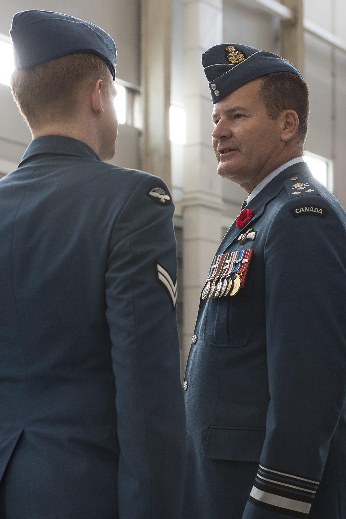 Corporal Trevor Archer of 429 Transport Squadron (left) speaks with RCAF commander Lieutenant-General Michael Hood during a November 7, 2017, parade held at 8 Wing Trenton, Ontario, to mark the squadron's 75th anniversary. PHOTO: Ordinary Seaman Paul Green, TN05-2017-0661-100