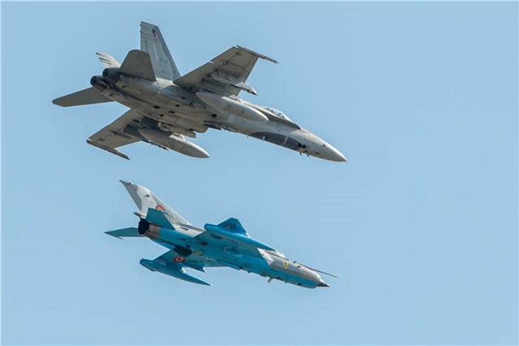 Two different fighter aircraft carry out a flypast.