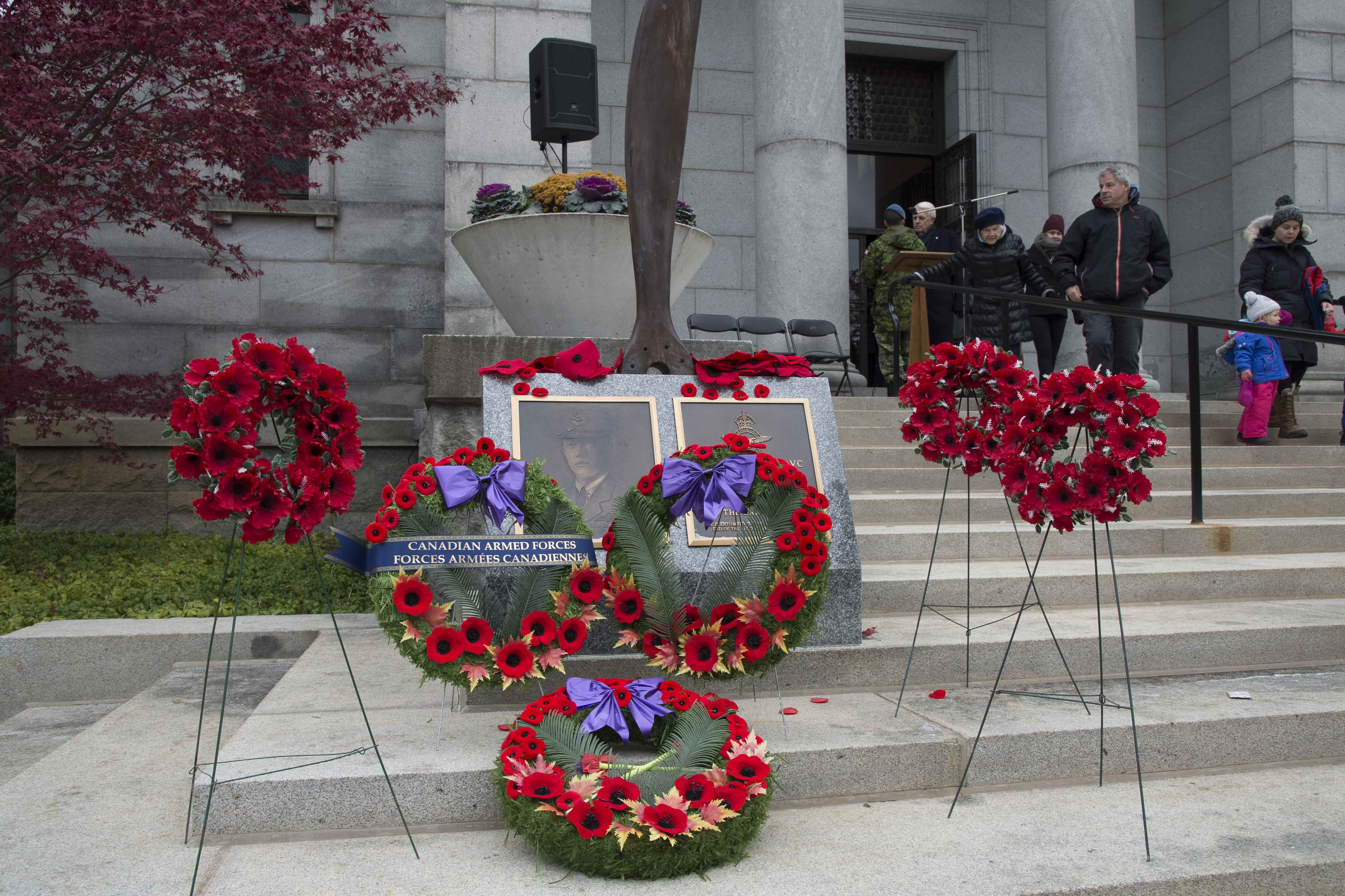 Wreaths of poppies lie on gray steps in front of a memorial.