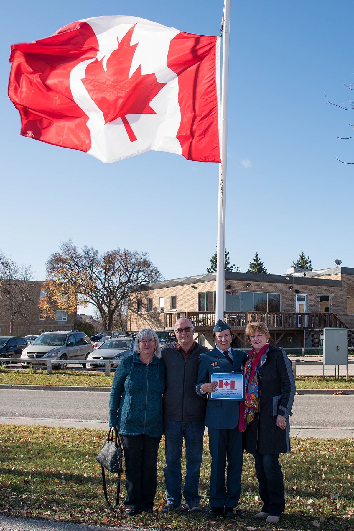 On October 13, 2017, her last day in uniform, Captain Cathy Coombs gathers with her husband and sisters under her raised flag at 17 Wing Winnipeg. From left, Rita Pierre, Alan Coombs, Captain Cathy Coombs and Susan Holland. PHOTO: Corporal Justin Ancelin, WG2017-0377-003