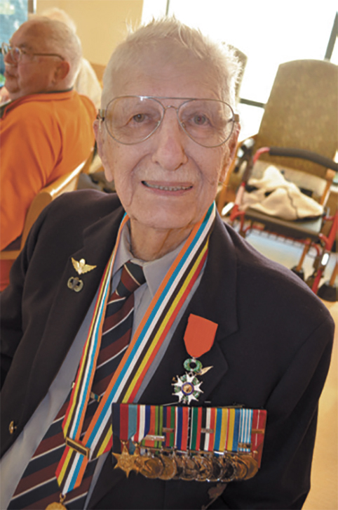 An elderly man sits, wearing a blazer bearing many medals on ribbons.