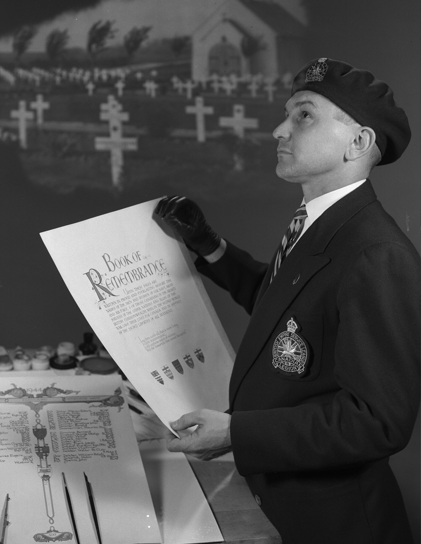 "In a black and white photo, a man in a blazer and beret wears one black glove and holds a large sheet of paper titled ""Book of Remembrance""; a photo of a cemetery is projected on the wall beside him."