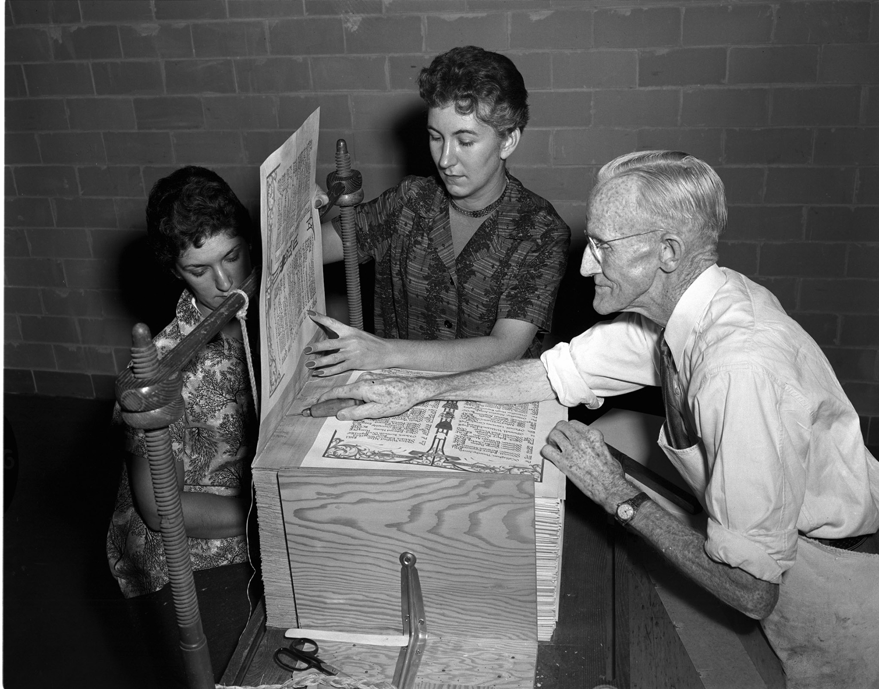 In early autumn 1957, Queen's Printers stitchers Lise Denis (left) and Ninette Denis, of Hull, Québec, and bookbinder Daniel Darragh, of Ottawa, Ontario, put the final touches on Canada's Second World War Book of Remembrance, which records the names of 44,891 Canadian servicemen and servicewomen who gave their lives during that war. This Book of Remembrance was dedicated on Remembrance Day, November 11, 1957, by Governor General and Commander-in-Chief of Canada Vincent Massey in the Memorial Chamber of the Parliament Buildings in Ottawa. PHOTO: DND Archives, AZ-8141-22