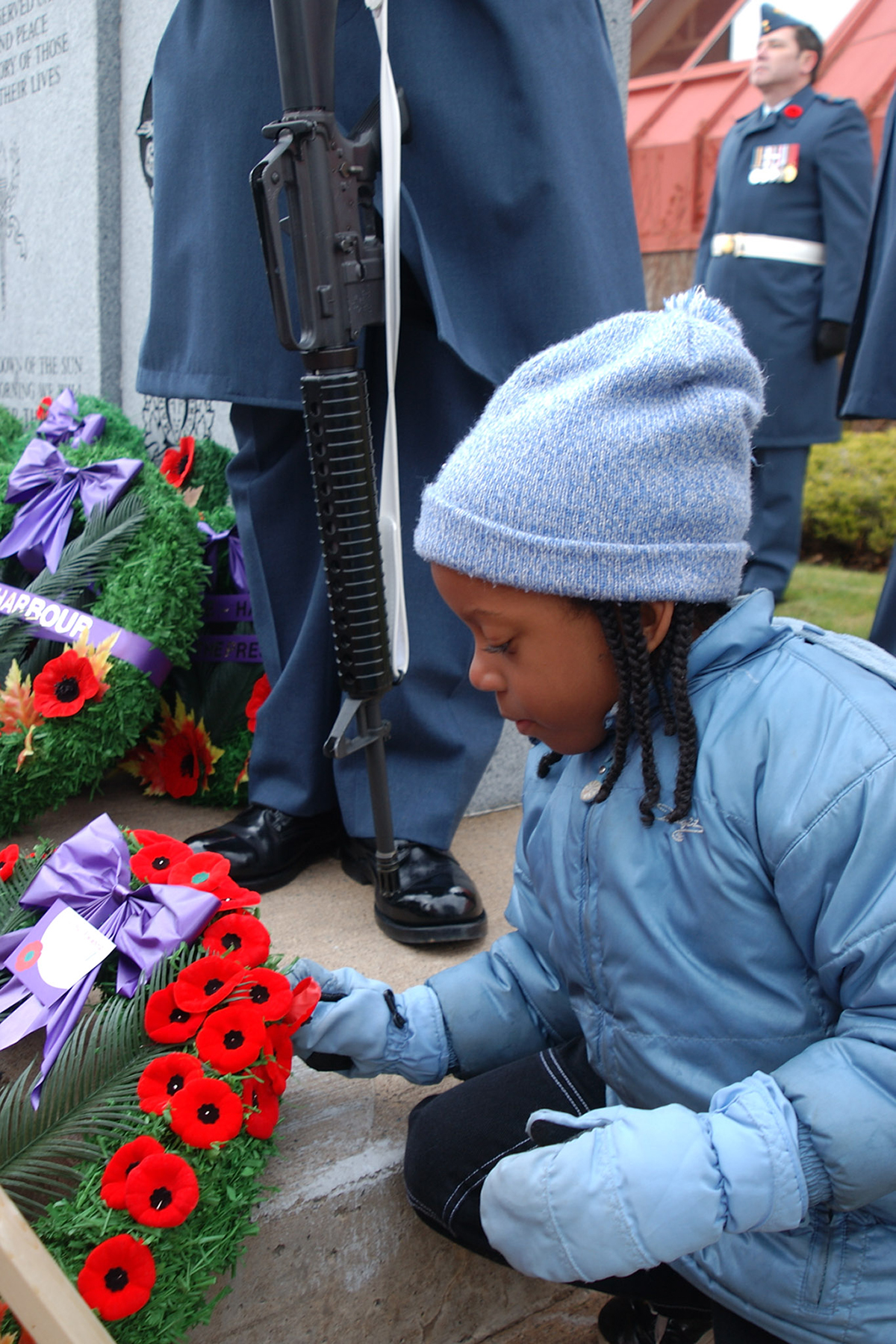 A child places her poppy on a wreath following the November 11, 2004, Remembrance Day ceremony hosted by Centennial Branch #160 of the Royal Canadian Legion in Cole Harbour, Nova Scotia. PHOTO: Corporal Claude Flibotte, SW2004-0483-05a