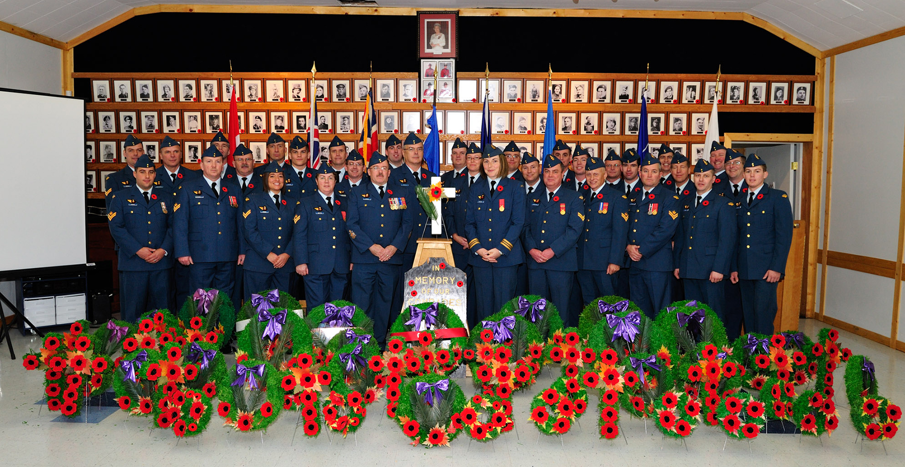 Members of 10 Field Technical Training Squadron stand in front of a wall of photographic portraits of war veterans at 4 Wing Cold Lake, Alberta, after taking part in the Mallaig, Alberta, Legion Remembrance Day ceremony held on November 11, 2009. PHOTO: Master Corporal Kelly Low, FT2009-0080-23