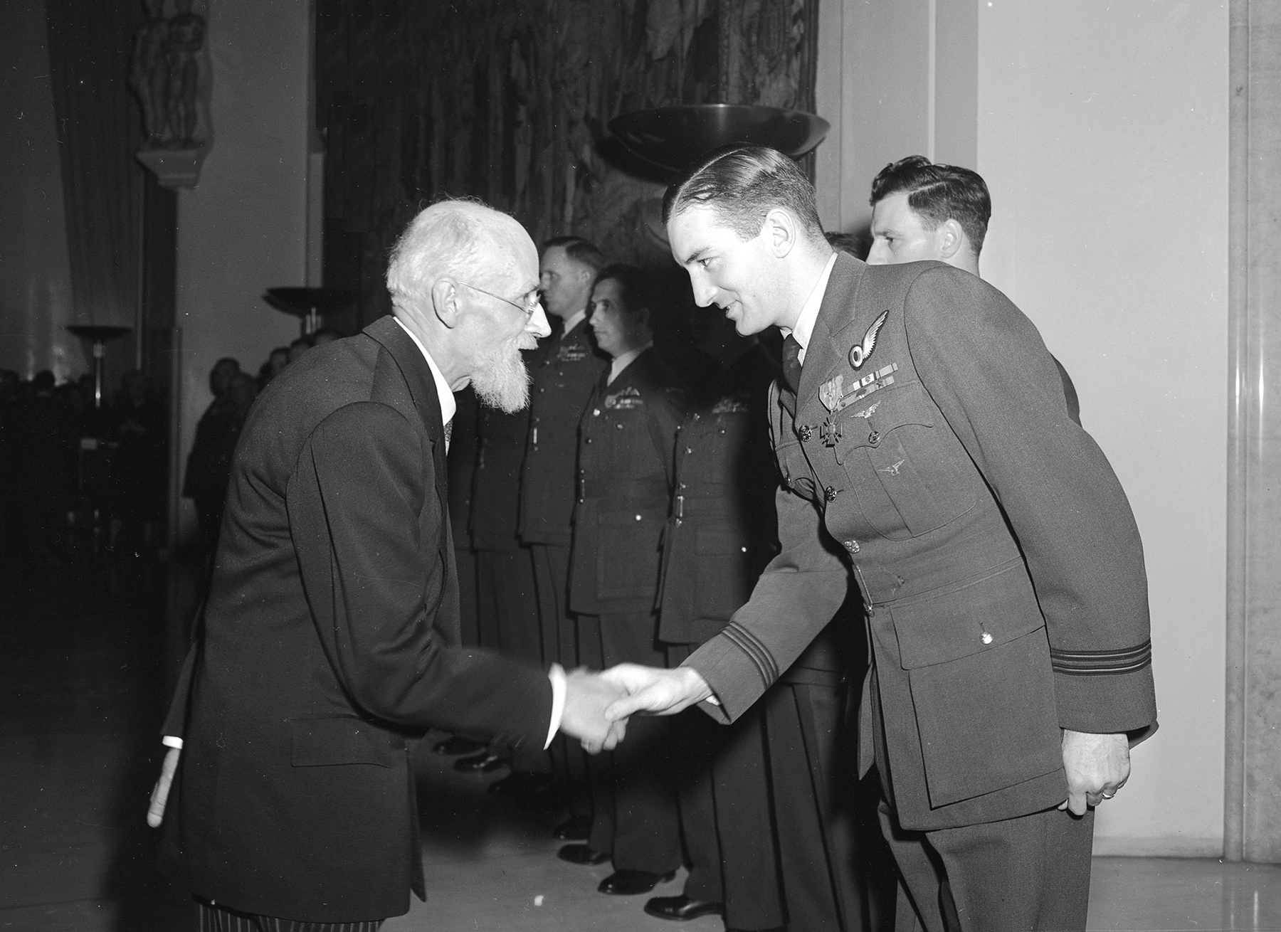 Flight Lieutenant A.M. Ogilvie, DFC, is congratulated by France's Ambassador Francisque Gay on Remembrance Day, November 11, 1947, after having received the Croix de Guerre with Gilt Star and having been cited to the Ordre de le Brigade Aerienne of France. Sixteen RCAF officers were honoured during the ceremony held at the French Embassy in Ottawa, Ontario. PHOTO: DND Archives, PL-39418